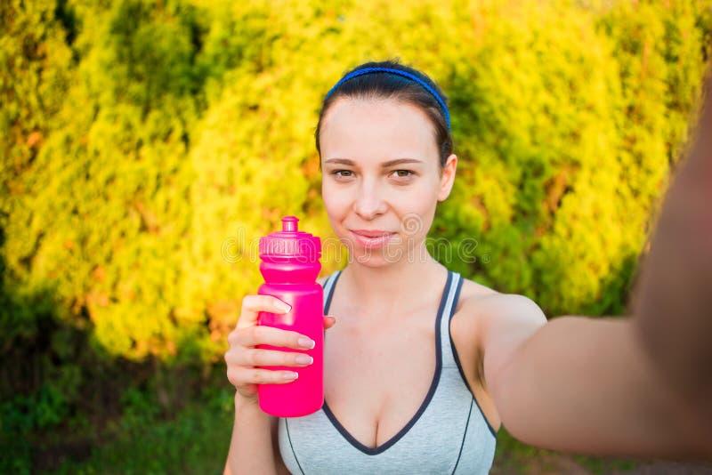 Jonge vrouw met fles water na buiten het lopen Vrouwelijke geschiktheid model opleiding buiten en het nemen selfie in stock afbeelding