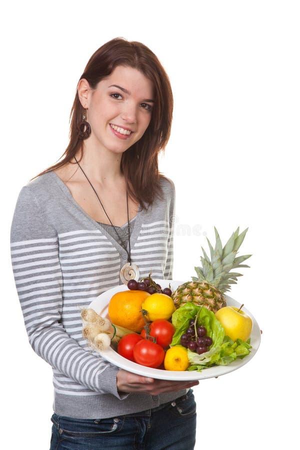 Jonge vrouw met fruit-gevulde kom in hun handen stock foto's