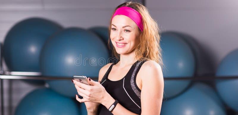Jonge vrouw met geschiktheidsdrijver bij de gymnastiek, trainingonderbreking stock foto's
