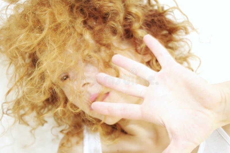 Jonge vrouw met gezicht dat door krullend haar wordt verborgen royalty-vrije stock afbeelding