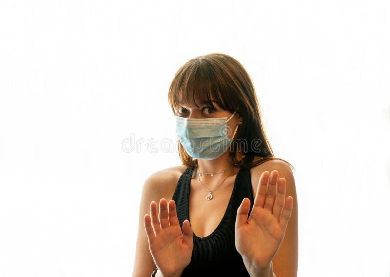 Jonge vrouw met gezichtsmasker dat van camera's afstaat terwijl ze beide handen op een beschermende manier heeft opgehangen royalty-vrije stock foto