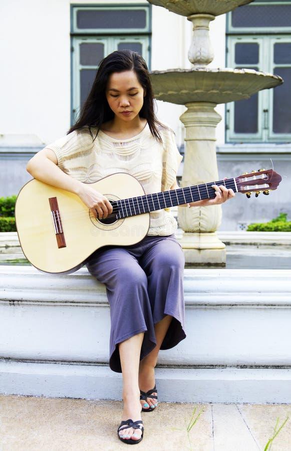 Jonge vrouw met gitaar stock foto