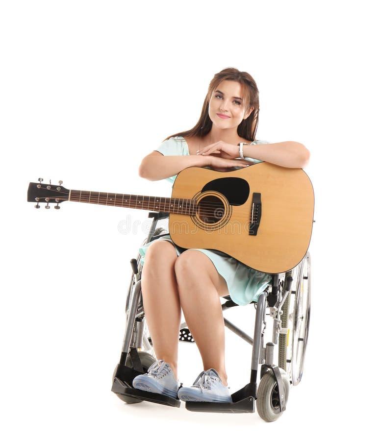 Jonge vrouw met gitaarzitting in rolstoel op witte achtergrond royalty-vrije stock afbeeldingen