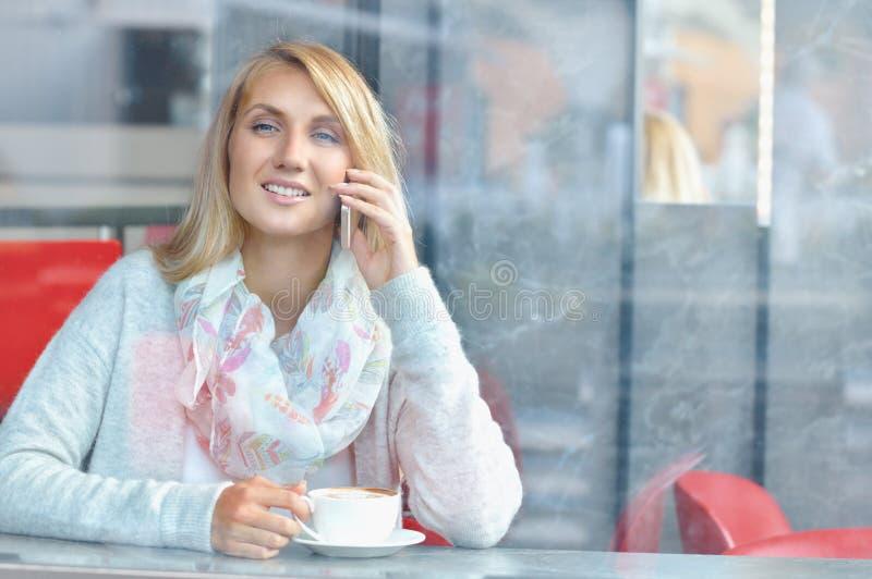 Jonge vrouw met glimlach die mobiel telefoongesprek hebben terwijl het rusten in koffie stock afbeeldingen