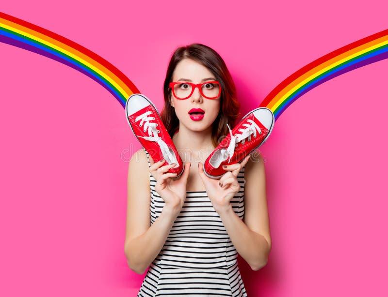 Jonge vrouw met gumshoes en regenboog stock afbeelding