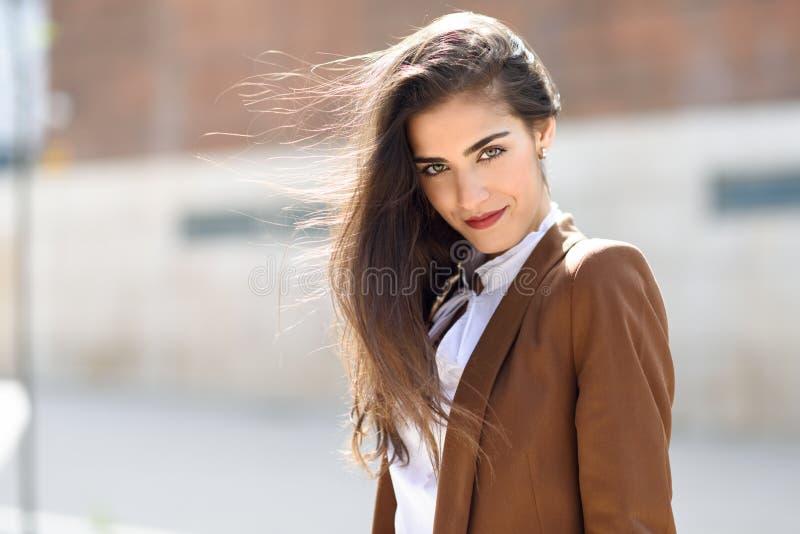 Jonge vrouw met haar in de wind op stedelijke achtergrond stock foto
