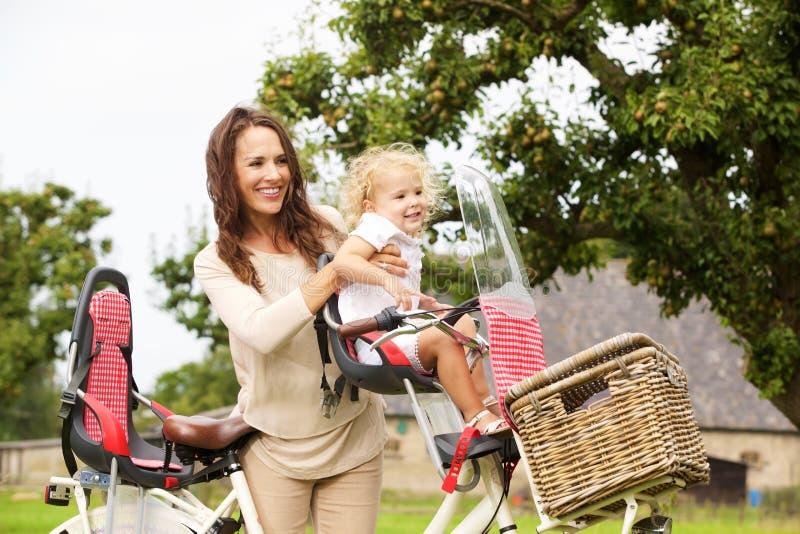 Jonge vrouw met haar dochter op fiets in het park stock afbeelding