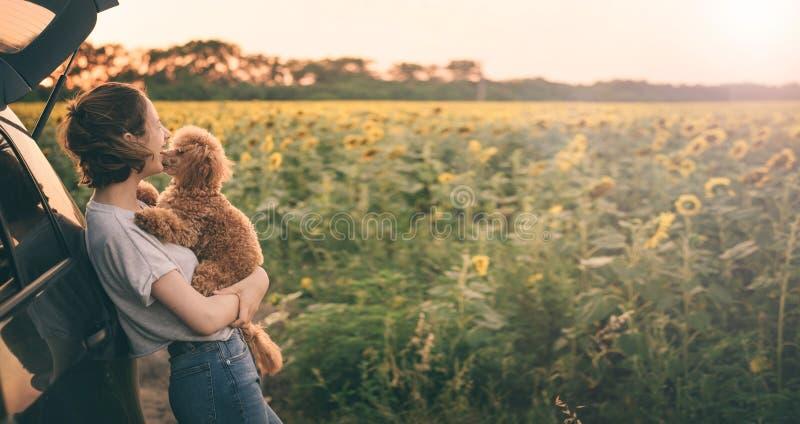 Jonge vrouw met haar hond die zich dichtbij de auto bevinden stock afbeeldingen