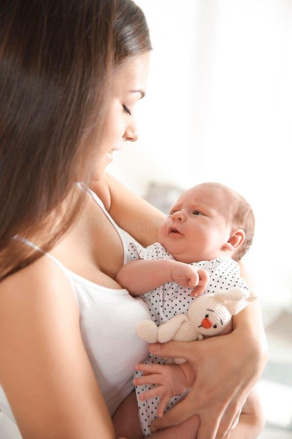 Jonge vrouw met haar pasgeboren baby stock foto