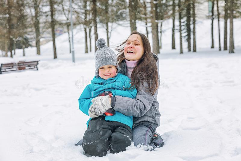 Jonge vrouw met haar weinig zoon die in de sneeuw in de winter spelen stock foto