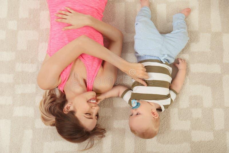Jonge vrouw met haar zoon die op vloer thuis liggen stock foto's