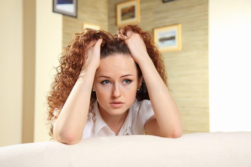 Jonge vrouw met handen op haar hoofd stock fotografie