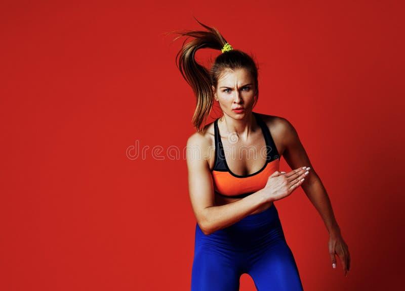 Jonge vrouw met het geschikte lichaam springen en het lopen tegen grijze achtergrond royalty-vrije stock foto