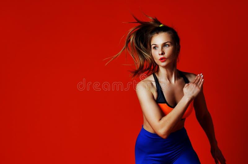Jonge vrouw met het geschikte lichaam springen en het lopen tegen grijze achtergrond stock fotografie