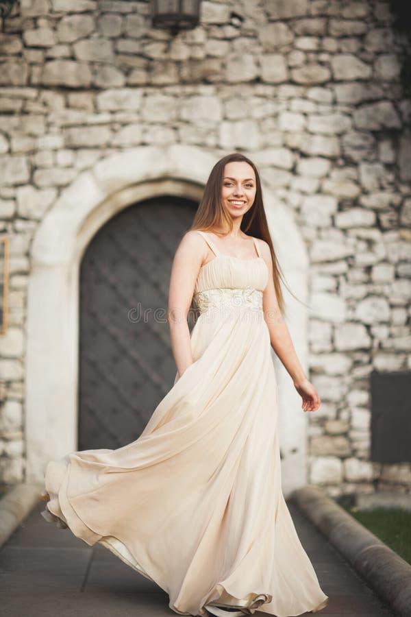 Jonge vrouw met het lange kleding en haar stellen in park dichtbij oude poort stock foto's