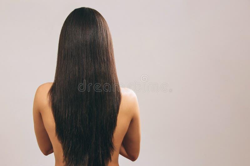 Jonge vrouw met het lange zwarte haar stellen op camera Het tonen van lengte van het Vlotte schat Status terug naar camera nanome stock fotografie