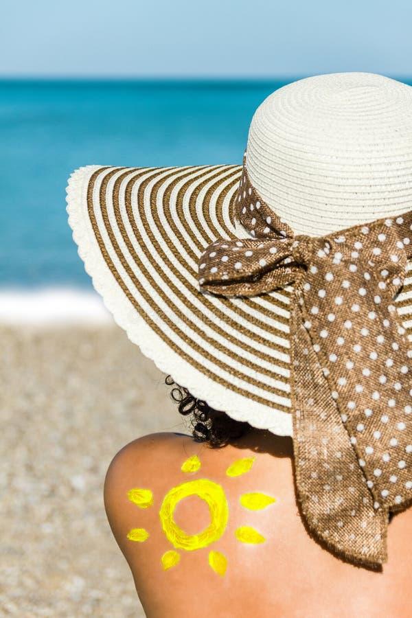 Jonge vrouw met hoedenzitting op het strand stock afbeelding