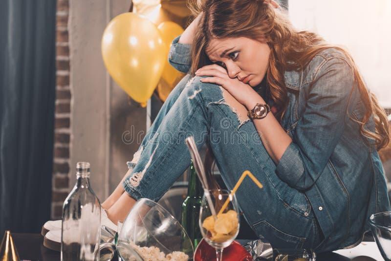 Jonge vrouw met hoofdpijn in slordige ruimte stock afbeeldingen