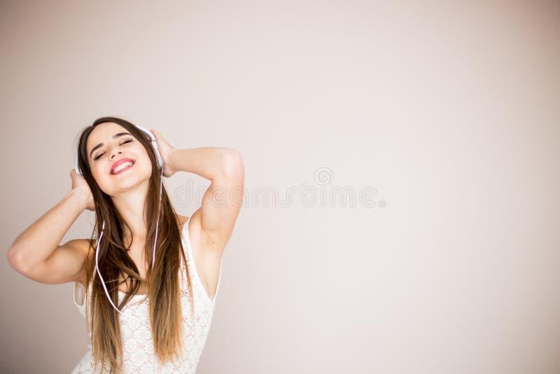 Jonge vrouw met hoofdtelefoons het luisteren muziek Het meisje die van de muziektiener tegen geïsoleerd dansen royalty-vrije stock afbeelding