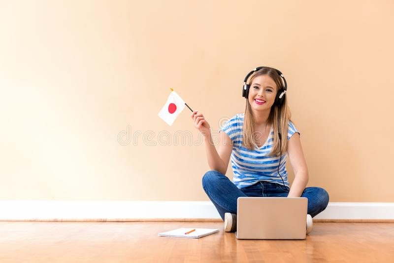 Jonge vrouw met Japanse vlag die een laptop computer met behulp van royalty-vrije stock foto