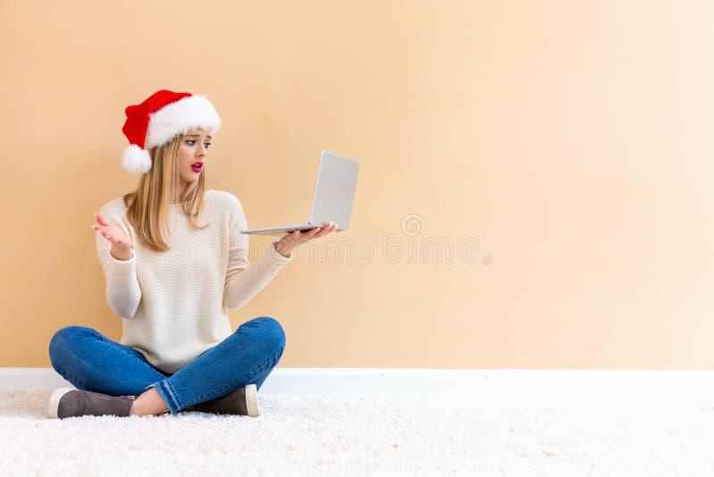 Jonge vrouw met Kerstmanhoed die haar laptop met behulp van stock afbeeldingen
