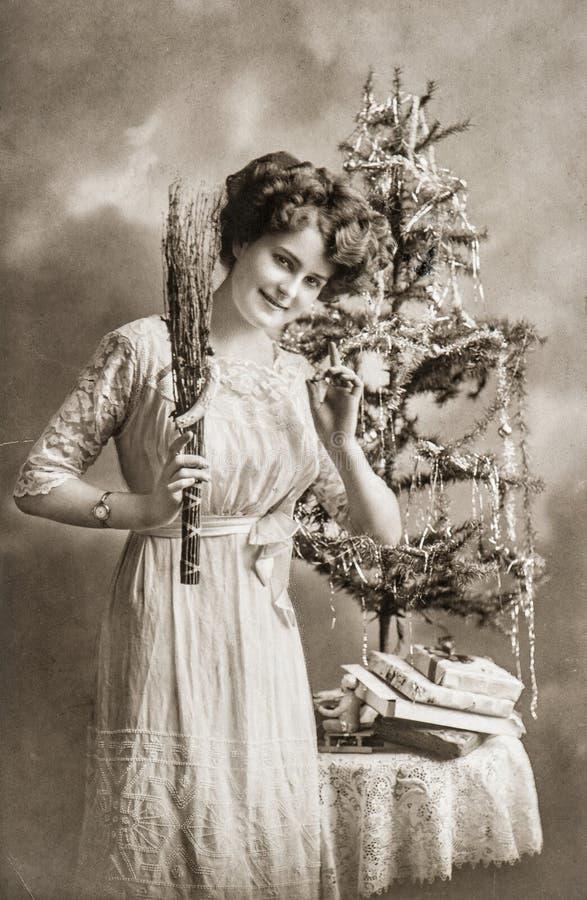 Jonge vrouw met Kerstmisboom en giften Antiek Beeld stock afbeeldingen