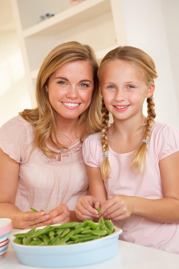 Jonge vrouw met kind verdelende erwt in keuken royalty-vrije stock foto