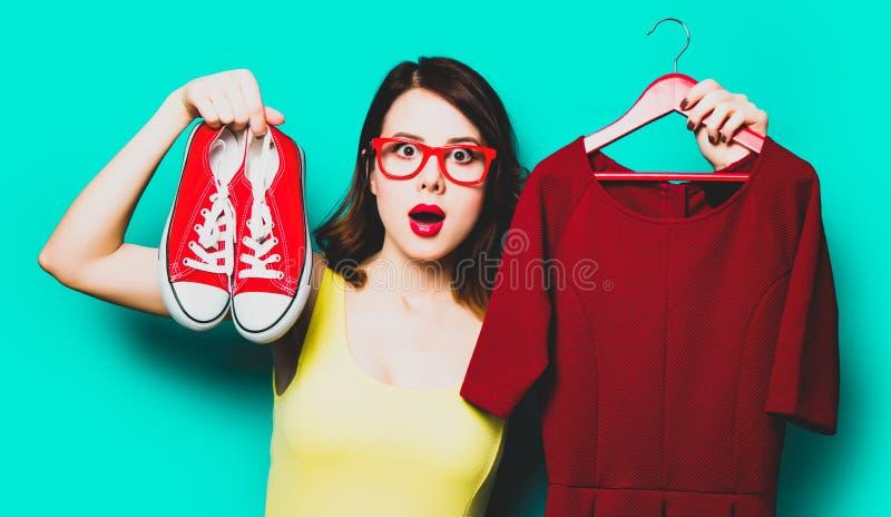 Jonge vrouw met kleding op hanger en gumshoes stock afbeeldingen