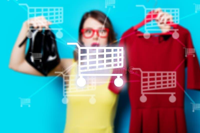 Jonge vrouw met kleding op hanger en schoenen stock foto