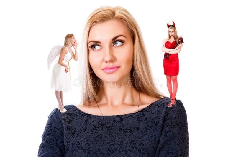 Jonge vrouw met kleine engel en demon op haar schouders stock foto