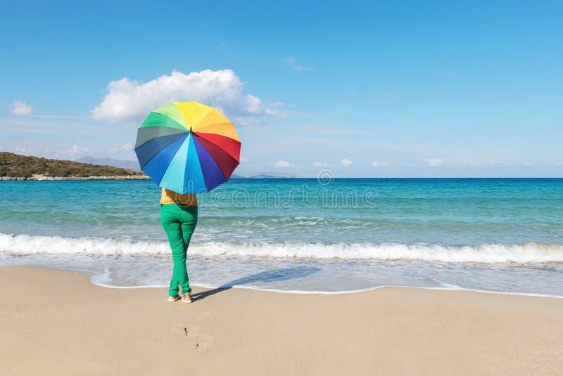 Jonge vrouw met kleurrijke paraplu op het strand stock foto's