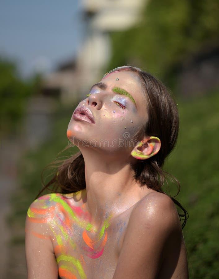 Jonge vrouw met kleurrijke verf en gesloten ogen stock afbeeldingen
