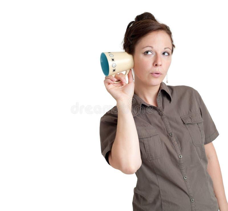 Jonge vrouw met koffiekop die naast haar oor wordt gehouden stock foto