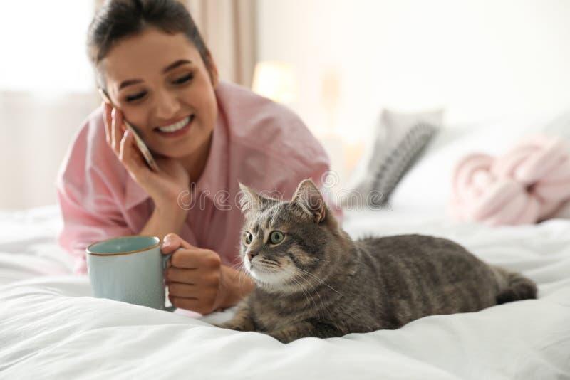 Jonge vrouw met kop die van koffie op telefoon spreken terwijl het liggen dichtbij leuke kat in slaapkamer royalty-vrije stock fotografie