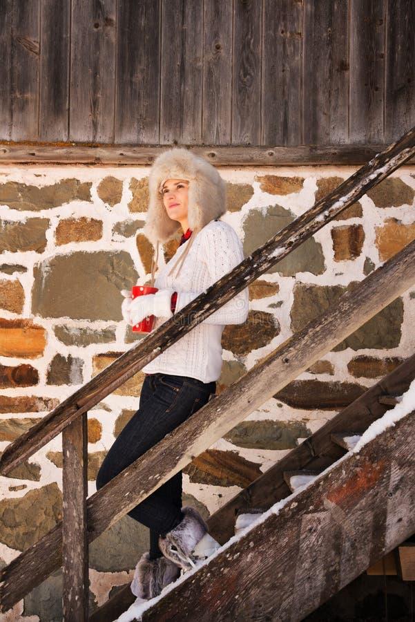 Jonge vrouw met kop die zich op treden van comfortabel berghuis bevinden stock afbeelding