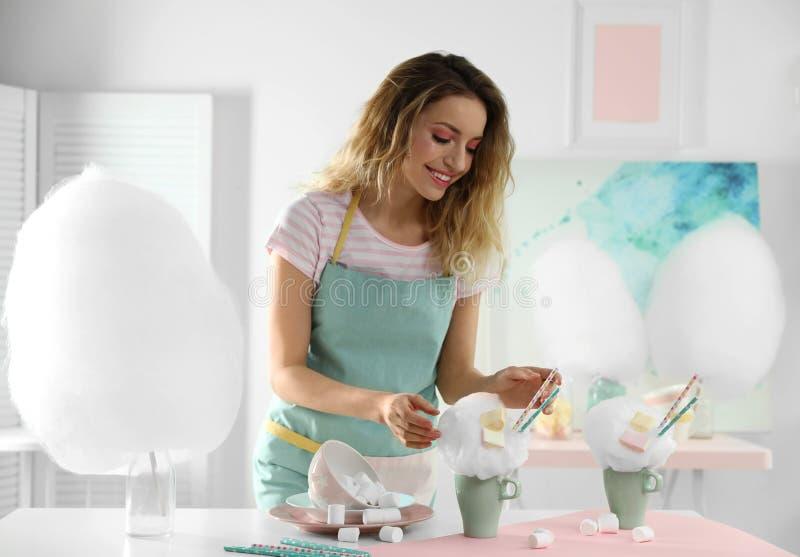 Jonge vrouw met kop van gesponnen suikerdessert bij lijst royalty-vrije stock afbeeldingen