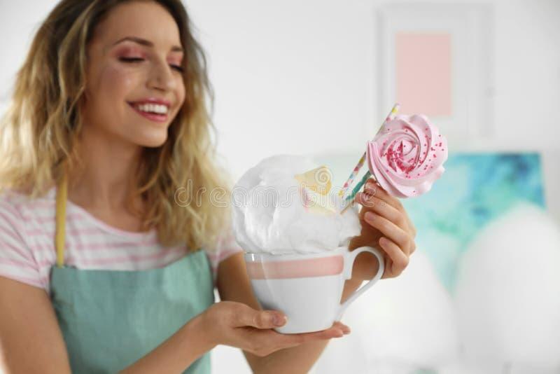 Jonge vrouw met kop van gesponnen suikerdessert stock foto