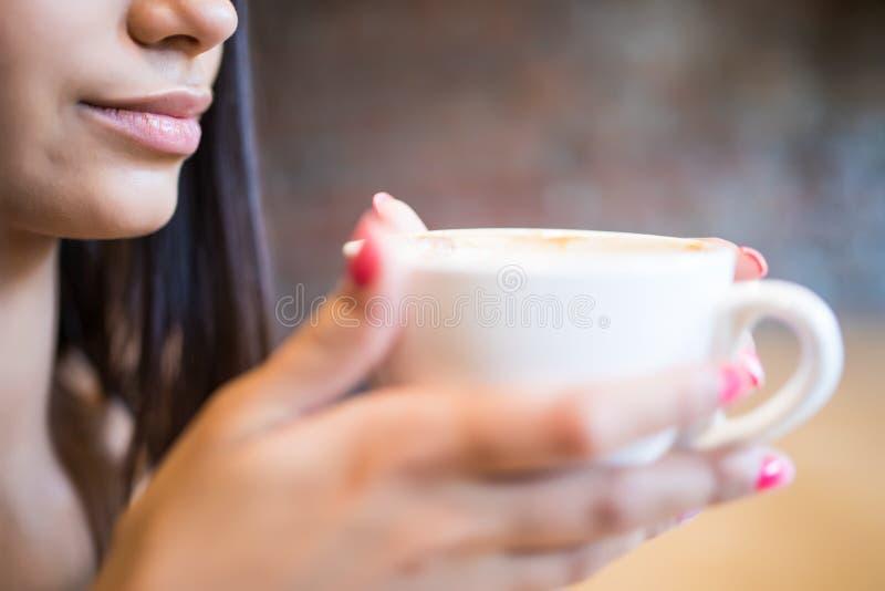 Jonge vrouw met kop van koffie in handen vóór drank stock foto