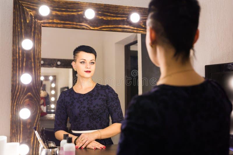 Jonge vrouw met kort haar zelf die bezinning in spiegel kijken royalty-vrije stock fotografie