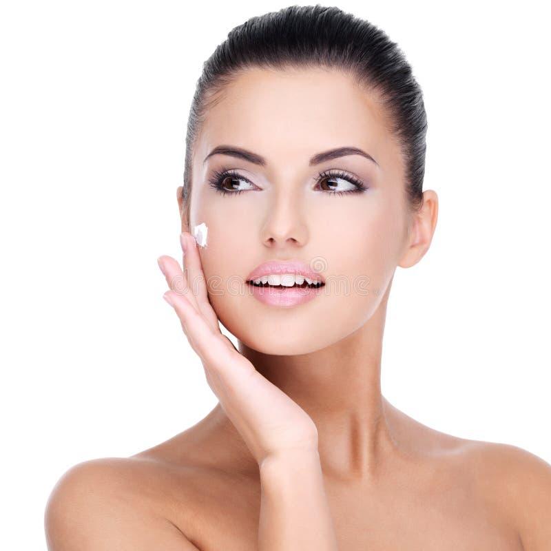 Jonge vrouw met kosmetische room op gezicht royalty-vrije stock foto's