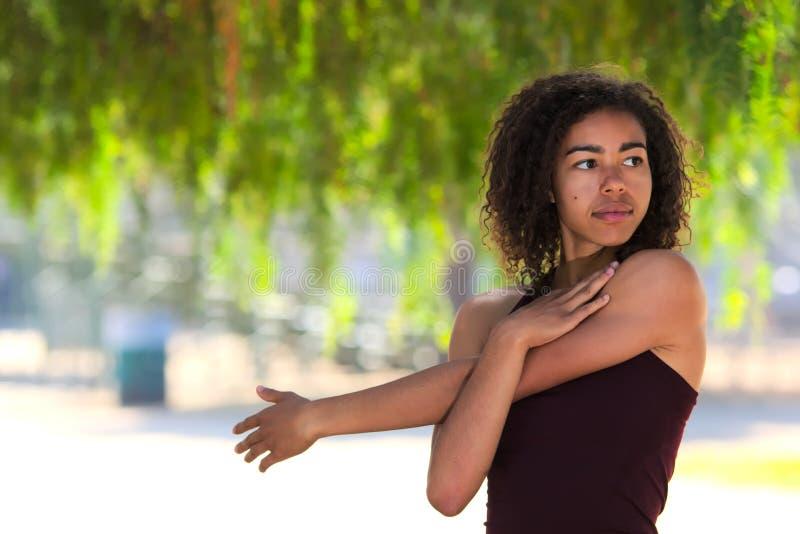 Jonge vrouw met krullend haar die zich buiten uitrekken royalty-vrije stock foto's