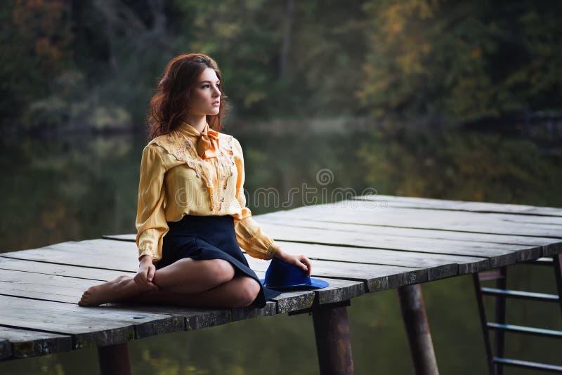 Jonge vrouw met krullende haarzitting op houten pijler stock afbeeldingen