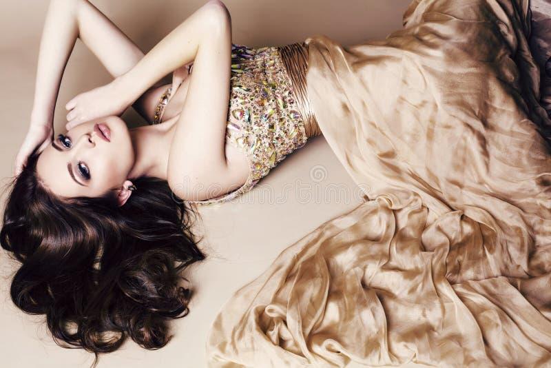 Jonge vrouw met lang donker haar die luxueuze lovertjekleding dragen royalty-vrije stock fotografie