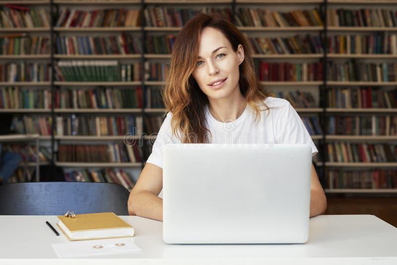 Jonge vrouw met lang haar die aan laptop op mede-werkt kantoor of bibliotheek, boekenrek erachter werken Onderneemster die een bo stock foto's