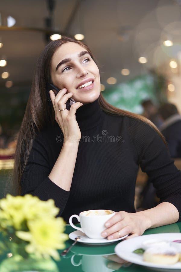 Jonge vrouw met lang haar die door mobiele smartphone met kop van koffie spreken, die rust in koffie hebben dichtbij venster stock afbeeldingen