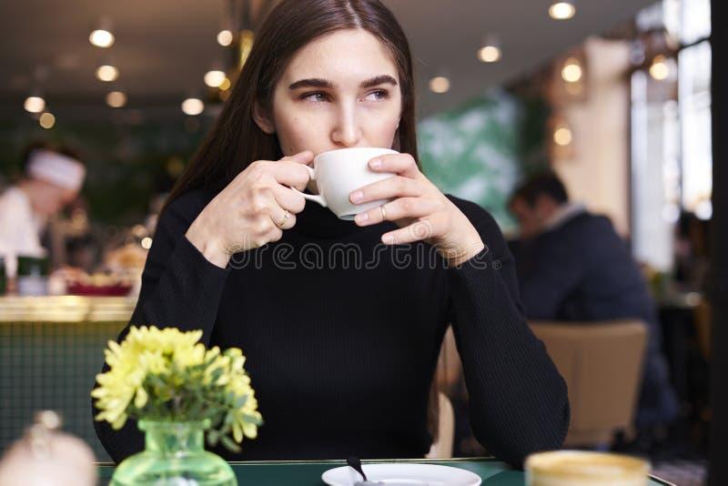 Jonge vrouw met lang haar in zwart Jersey met kop van koffie in handen die rust in koffie hebben dichtbij venster stock foto