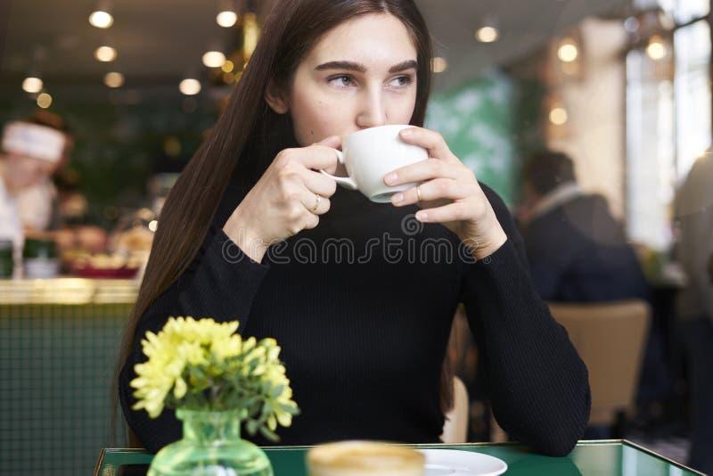 Jonge vrouw met lang haar in zwart Jersey met kop van koffie in handen die rust in koffie hebben dichtbij venster royalty-vrije stock fotografie