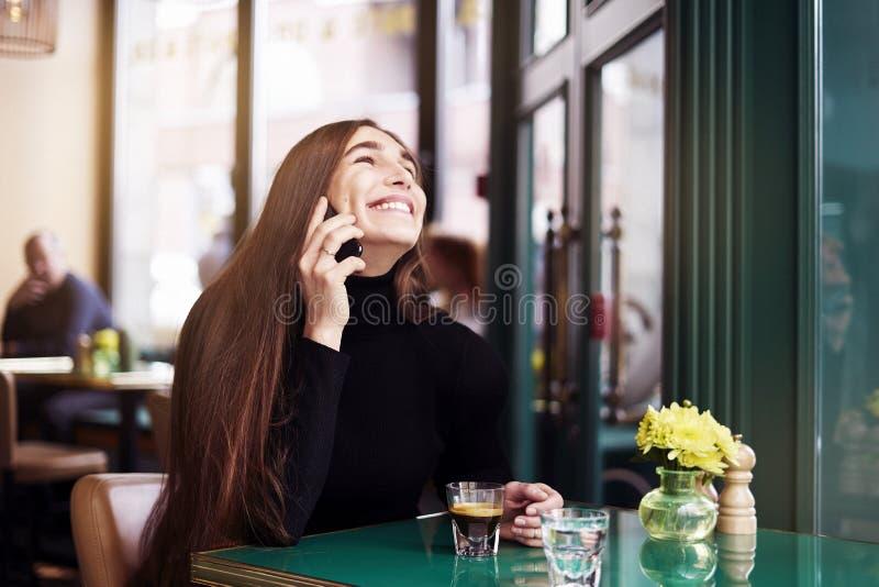 Jonge vrouw met lange haarlach en glimlach, het drinken koffie die rust in koffie hebben dichtbij venster stock foto