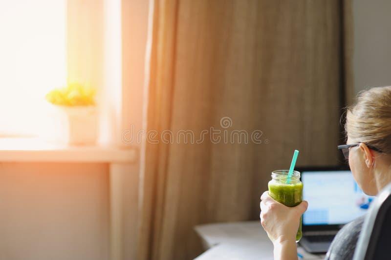 Jonge vrouw met laptop bij houten lijst Drinkende groene smoothie stock fotografie