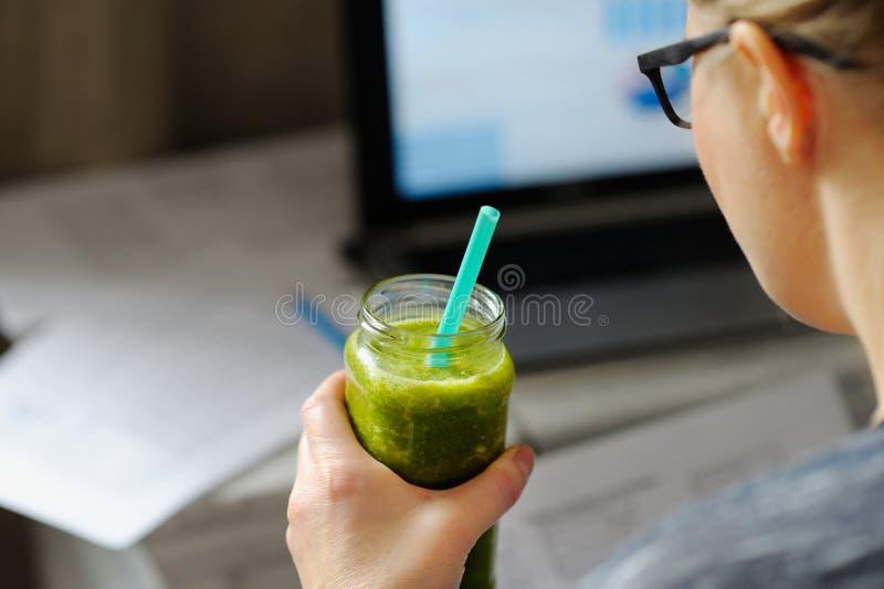 Jonge vrouw met laptop bij houten lijst Drinkende groene smoothie royalty-vrije stock afbeelding